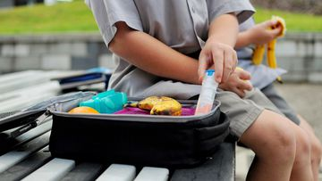 Child with EpiPen in lunch box