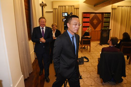 Victoria and Tasmania Consul-General of China Long Zhou (centre) departs a press conference at the Commonwealth Parliamentary Offices in Melbourne.