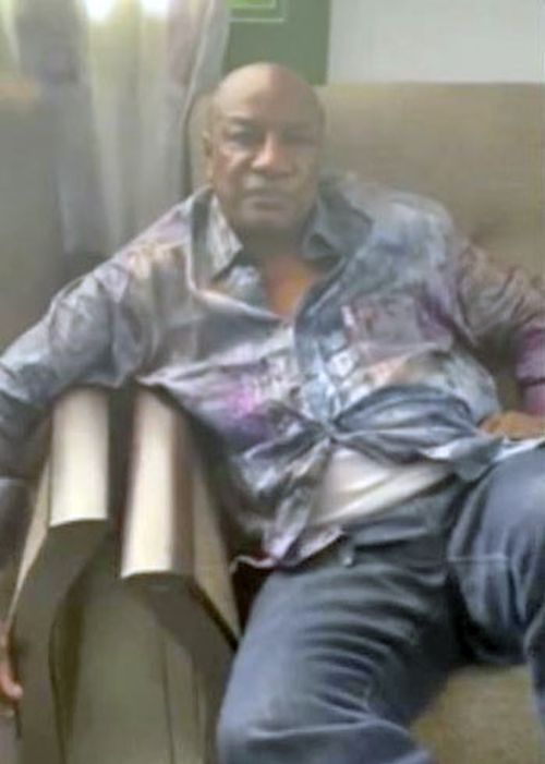In this image made from a video released on Sunday, Guinean President Alpha Conde sits on a sofa in an unknown location.