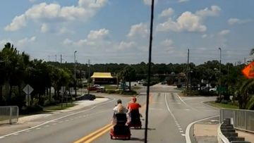 An elderly couple have held up traffic heading to the beach in Florida by riding their electric scooters down the highway.