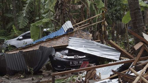 Cars are covered by debris at an area ravaged by a tsunami, in Carita, Indonesia.
