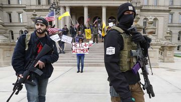 Protesters brandish assault rifles and swastikas at a rally opposing Michigan lockdown laws.