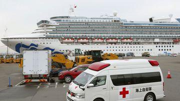 An ambulance leaves Yokohama Port where the Diamond Princess, back, is docked in Yokohama, near Tokyo, Friday, Feb. 14, 2020. The cruise ship is still carrying nearly 3,500 passengers and crew members under quarantine until at least Feb. 19.