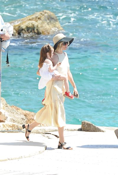 <p>Paying homage to the Riveria, Miller wears an elegant cream sun dress, black sandals and a wide-brim hat during downtime.</p>