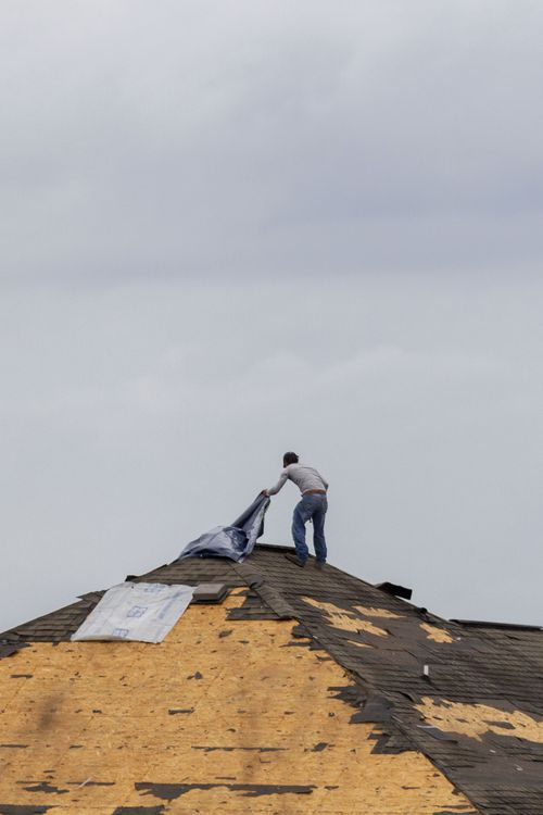 A worker checks the damage to the roof of a house being built along State Road 69 as tornado activity hits Alabama. (AP Photo/Vasha Hunt)