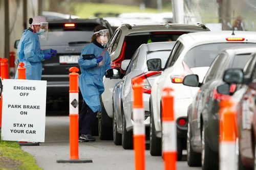 MELBOURNE, AUSTRALIA - JULY 19: Cars are seen lining up at  drive through testing site at Albert Park Lake on July 19, 2021 in Melbourne, Australia. Lockdown restrictions have come into effect across Victoria as health authorities work to contain two COVID-19 outbreaks linked to Sydney's delta strain coronavirus cluster. The snap five-day lockdown, which came into effect at midnight on Thursday, was called after more new COVID-19 cases and exposure sites were confirmed across the state. Under th