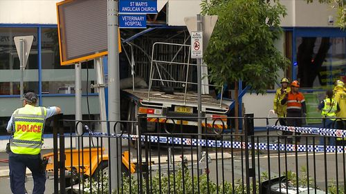 A truck has crossed a busy road and smashed into the side of a building in Sydney's west.