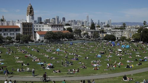 Visitors set up inside circles designed to help prevent the spread of the coronavirus at Dolores Park in San Francisco.