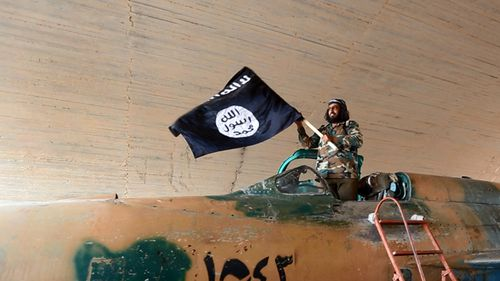 An Islamic State fighter (thought to be 2014) waving their flag from inside a captured government fighter jet following the battle for the Tabqa air base in Raqqa, Syria. (AAP)