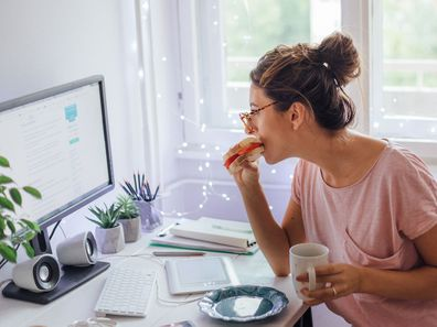 Woman eating while working from home.