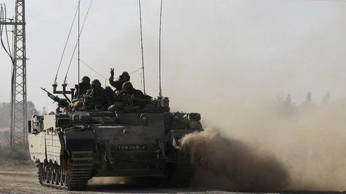 An Israeli tank drives along the border between Israel and Gaza. (AAP)