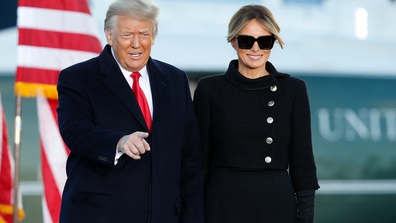 President Donald Trump gestures as first lady Melania Trump looks on before giving a speech to supporters at Andrews Air Force Base, Md., Wednesday, Jan. 20, 2021. (AP Photo/Luis M. Alvarez)