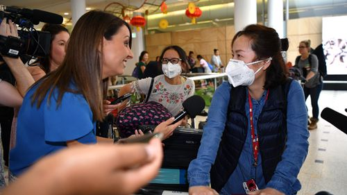 Passengers wearing protective masks arrive at Sydney International Airport on January 23. Australia is working to keep out the deadly coronavirus, as a flight from the Chinese city at the centre of the outbreak arrives in Sydney.