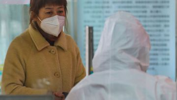 Medical workers in protective gear talk with a woman suspected of being ill with a coronavirus at a community health station in Wuhan in central China's Hubei Province.