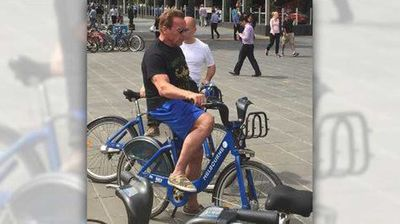 A helmetless Arnie  Schwarzenegger takes in the sights of Melbourne on a share bike.