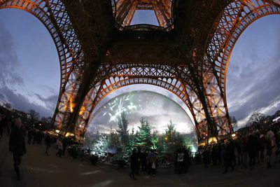 People gather around an installation of pine trees in a giant snow globe under the Eiffel Tower in Paris. (Francois Guillot/AFP/Getty)