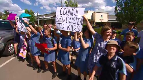 The kids made a noise outside the council building.