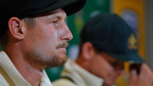 A grim-faced Cameron Bancroft speaks to the media with his sullen captain alongside. Picture: AAP