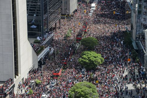Fans cheer during the Toronto Raptors NBA basketball championship victory parade in Toronto. (Andrew Lahodynskyj/The Canadian Press via AP)