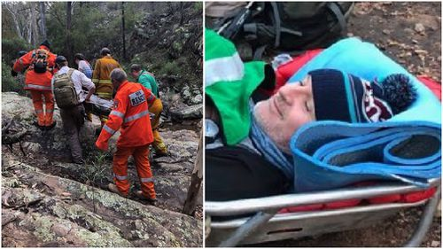 The former premier looked relatively relaxed as he was carried away with a broken leg. (9NEWS)