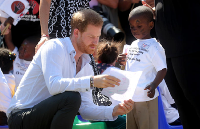 Prince Harry admires a drawing presented to him by the shy child.