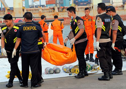 Police officers carry a body bag containing the remains recovered from the area where a Lion Air passenger jet crashed, at Tanjung Priok Port in Jakarta, Indonesia.