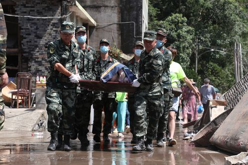 Chinese rescuers carry a victim after a landslide caused by the Typhoon Lekima.