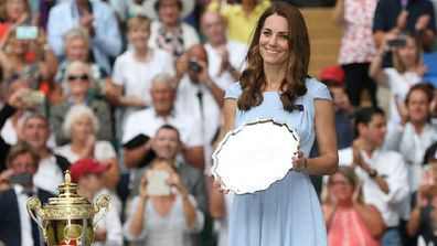 Roger Federer of Switzerland is about to be presented with the runners-up trophy by the Duchess of Cambridge in 2019.
