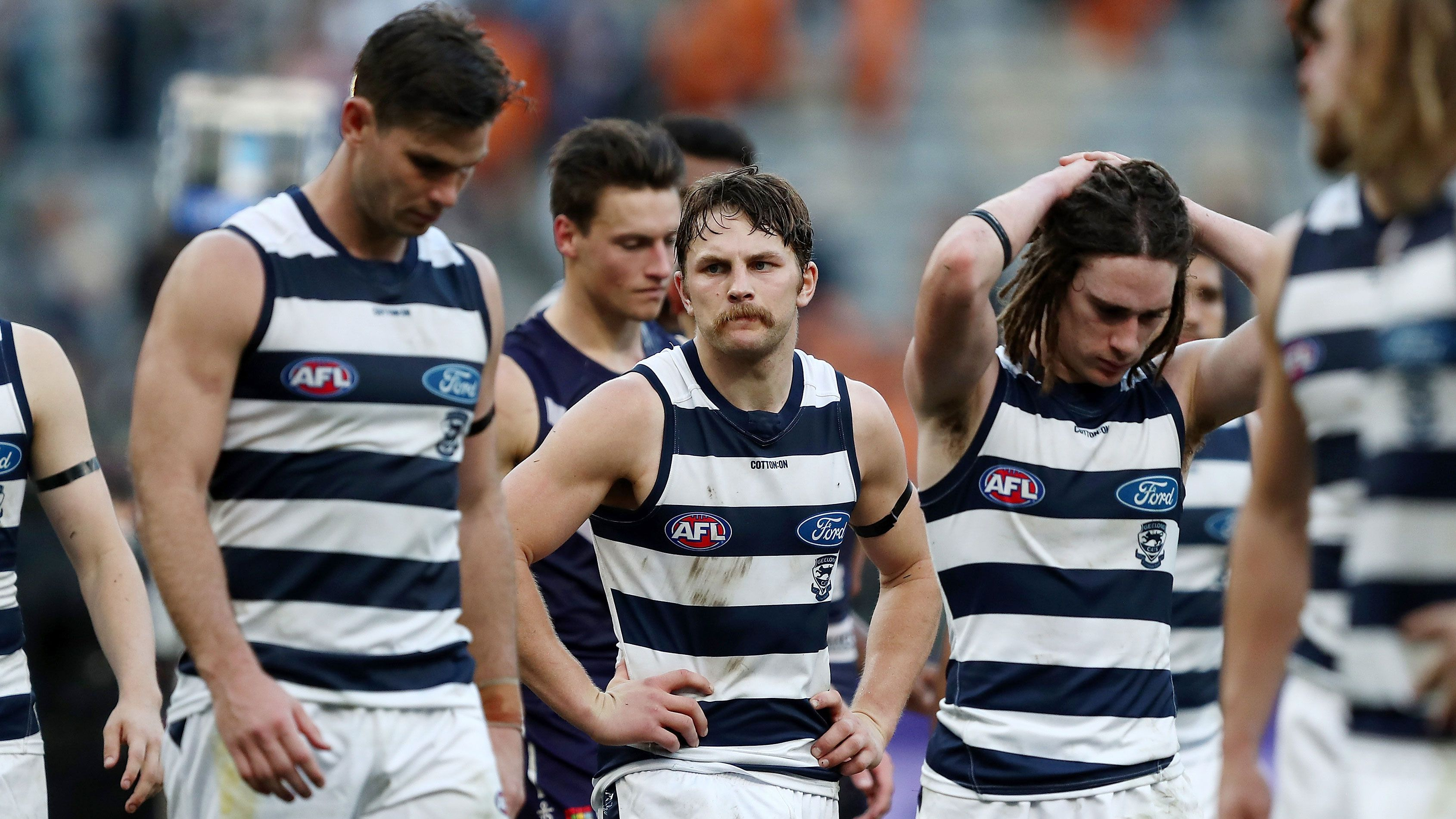 Geelong Cats players react to their loss to Fremantle.