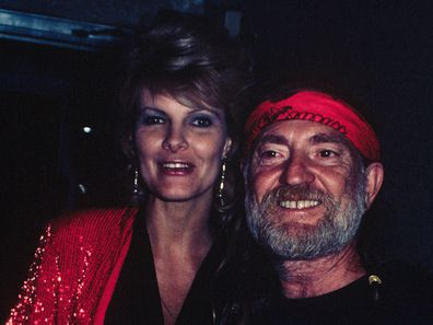 Willie Nelson with his wife Connie Keopke.  She is wearing a red sequined jacket; circa 1970; New York.