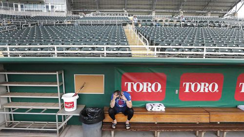 Minnesota Twins catcher Mitch Garver talks on his phone in an empty Hammond Stadium in Fort Myers, Florida, following the cancellation of all spring training games.