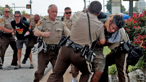 A man is arrested as the protests enter a second week. (AAP)