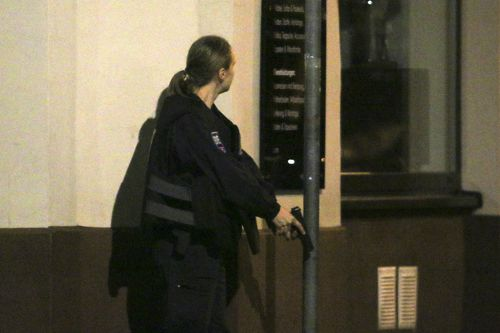A police officer stays in position with a gun at the scene after gunshots were heard, in Vienna
