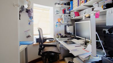 A shot of a messy desk in a home office, the room is small and cluttered.