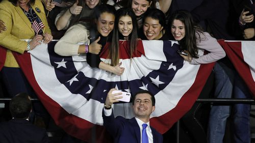 Pete Buttigieg takes a selfie with supporters at his election night rally in Iowa.