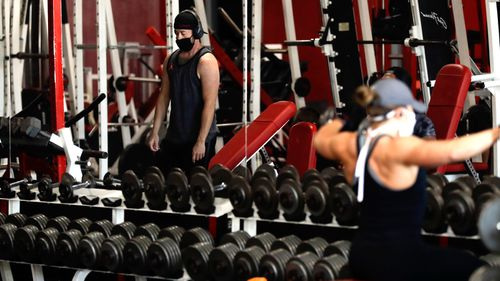 People work out at a gym wearing protective face masks and adopting social distancing measures.