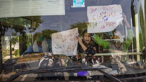 Indian activists hold placards and shout slogans from inside a bus after being detained during a protest in New Delhi.
