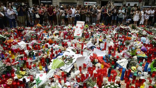 People stand next to candles and flowers placed on the ground after a terror attack in Barcelona. (AAP)