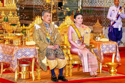 Thailand's King Maha Vajiralongkorn Bodindradebayavarangkun (Rama X), with Queen Suthida, sits under the Royal Nine-tiered Umbrella at Baisal Daksin Throne Hall in Bangkok.