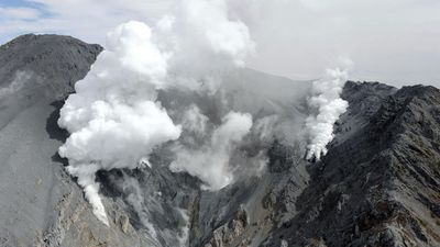 White plumes of gases and ash spew out of the summit crater. (AP Photo/Kyodo News)