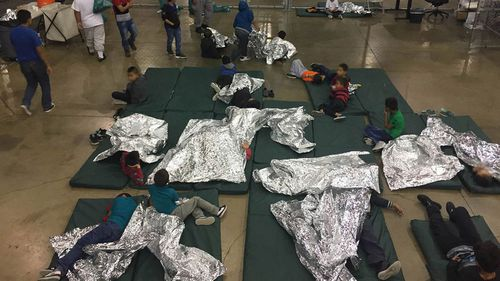 Children taken into custody related to cases of illegal entry into the United States, rest in one of the cages at a facility in McAllen, Texas. (AAP)