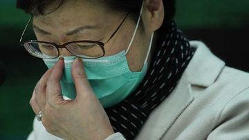 Hong Kong CEO Carrie Lam holds a press conference while wearing a face-mask.