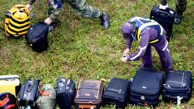 Rescue workers take photos of luggage recovered from the wreckage. (AAP)