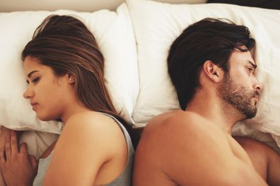Shot of a young couple lying in bed and ignoring each other