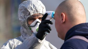 A Polish border guard dressed in a protective suit, mask and goggles takes the body temperature of a man seeking to enter Poland at the Polish/German border
