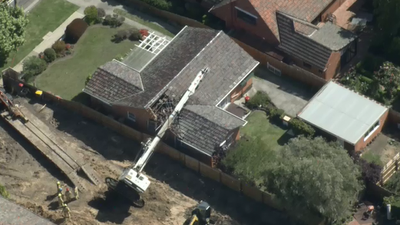 Drill rig topples onto home