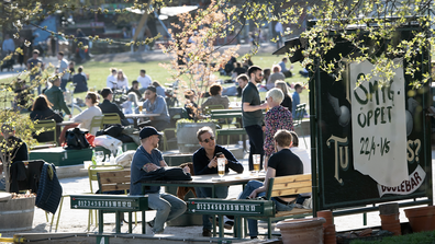 People gather for a drink at an outdoor bar in Stockholm, Sweden, Wednesday April 22, 2020 despite the coronavirus COVID-19 outbreak. (Anders Wiklund/TT via AP)