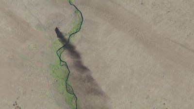 A black plume of smoke extends miles down from the largest oil refinery in Iraq, which was set on fire by insurgents who attacked the refinery earlier this year.