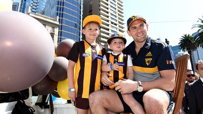 A Hawks player poses for a photo with some young fans. (AAP)