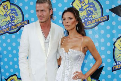 It amuses us that D-Becks' blinged-out crosses (on the outside of his crisp white suit), match VB's blinged-out bustier. <br/>